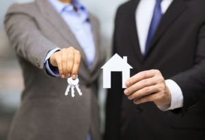 Real estate agents holding up new home keys and house cut out